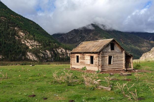 Schönes verlassenes blockhaus aus holz auf hintergrund der berge