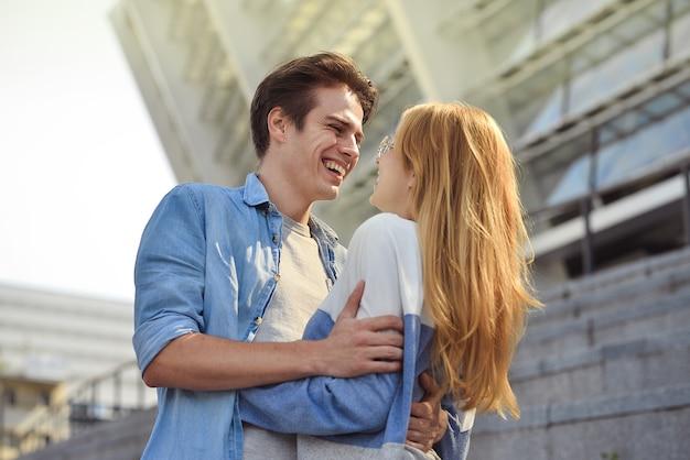 Schönes verliebtes paar, das draußen datiert und lächelt.