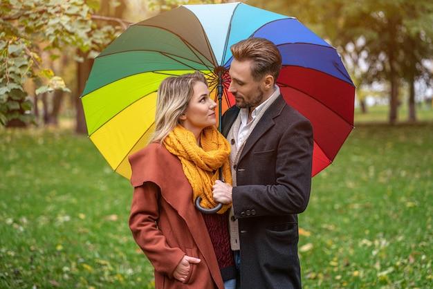Schönes verliebtes paar, das im park unter einem regenbogenfarbenen regenschirm steht, der einander augen betrachtet