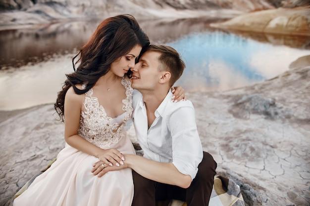 Schönes verliebtes paar, das sich auf den felsen küsst und umarmt