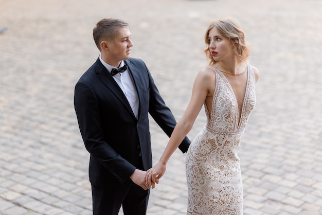 Schönes verliebtes paar in eleganter kleidung schaut sich leidenschaftlich an und hält im freien die hände zusammen