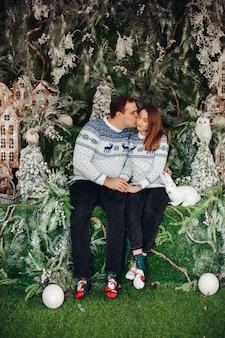 Schönes verliebtes paar in kuscheligen pullovern mit weihnachtsdruck, die zusammen küssen
