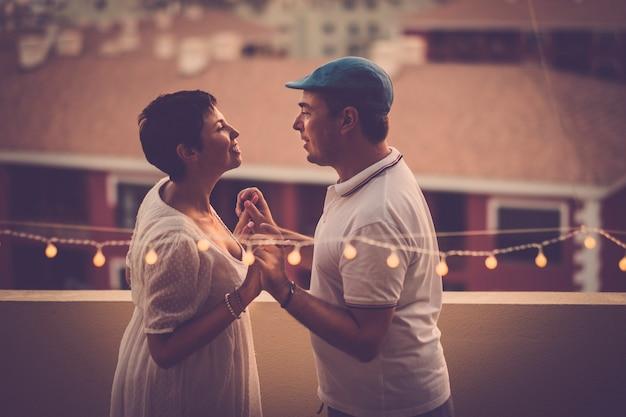 Schönes verliebtes paar mittleren alters, das sich gegenseitig lächelt und zu hause auf der terrasse mit herrlichem blick auf das haus von oben in die augen schaut