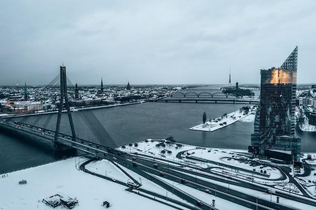 Schönes verschneites stadtbild von riga durch die vansu-brücke gesehen
