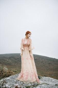 Schönes vertikales bild einer ingwerfrau mit einer reinen weißen haut in einem attraktiven rosa kleid