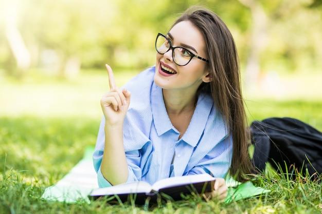 Schönes verträumtes jugendlich mädchen, das im park mit stift und notizbuch liegt