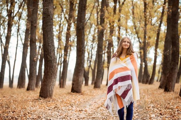 Schönes verträumtes mädchen, das im hellen herbstpark spazieren geht, die schönheit der natur bewundert und an etwas denkt. atmosphärisches herbstfoto