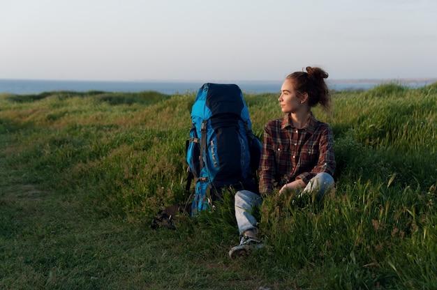 Schönes wanderer mädchen sitzt auf dem gras mit einem rucksack