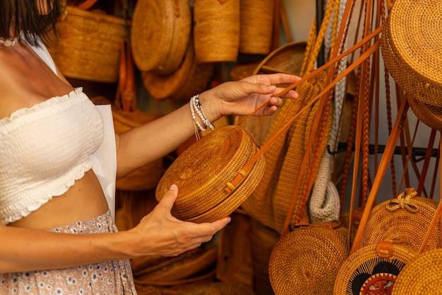 Schönes weibchen kommt, um souvenirs zu kaufen und eine korbtasche mit stäben und stroh auszuwählen
