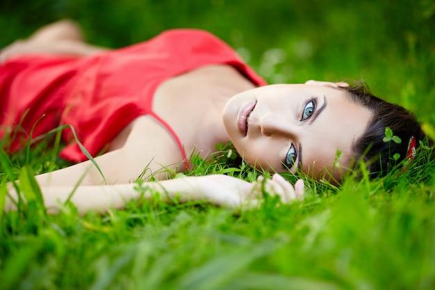 Schönes weibliches brünettes mädchenmodell, das im grünen sommerhellgras im park mit make-up im roten kleid liegt