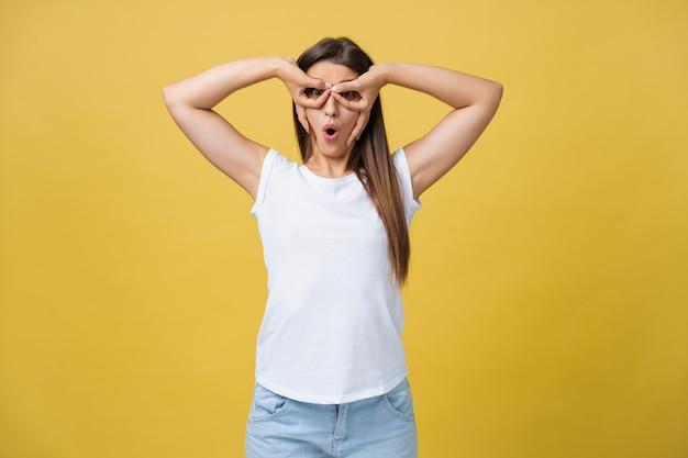 Schönes weibliches brustbild isoliert auf gelbem studiohintergrund. die junge emotionale lächelnde und überraschte frau, die kamera steht und betrachtet. die menschlichen gefühle, gesichtsausdruckkonzept
