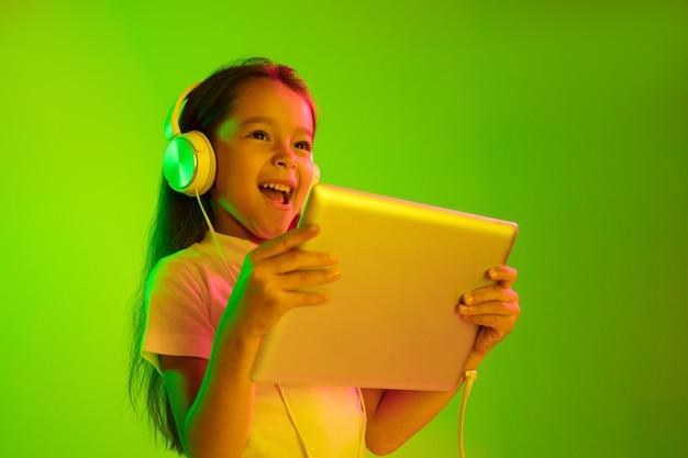 Schönes weibliches brustbild isoliert auf grünem hintergrund im neonlicht. junges emotionales mädchen. menschliche emotionen, gesichtsausdruckkonzept. trendige farben. tablet für spiele, vlog, selfie verwenden.
