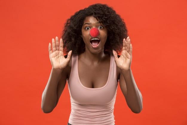 Schönes weibliches brustbild isoliert auf rotem studiohintergrund. junge überraschte frau, die tag der roten nase feiert und kamera betrachtet. menschliche emotionen, gesichtsausdruckkonzept. trendige farben