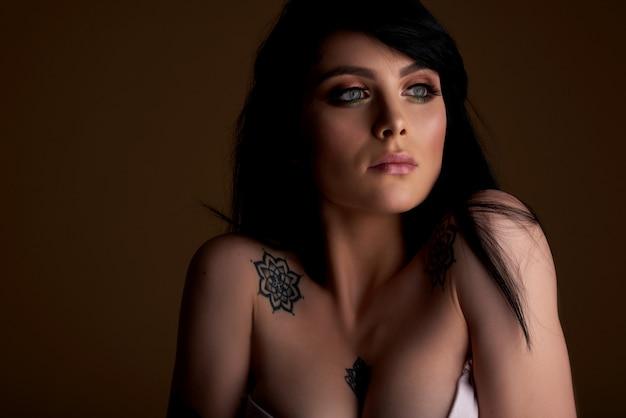 Schönes weibliches gesicht mit natürlicher perfekter haut, tätowierungshaut. tattoo mädchen.