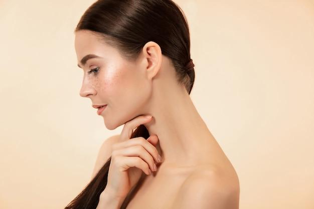 Schönes weibliches gesicht. perfekte und saubere haut der jungen kaukasischen frau auf pastellstudiohintergrund.