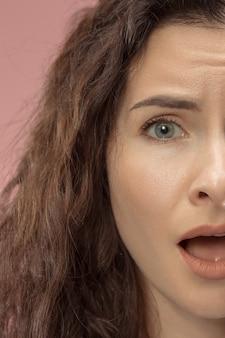 Schönes weibliches halbes gesichtsporträt lokalisiert auf trendigem rosa studiohintergrund. junge emotionale frustrierte und verwirrte frau. menschliche emotionen, gesichtsausdruckkonzept.