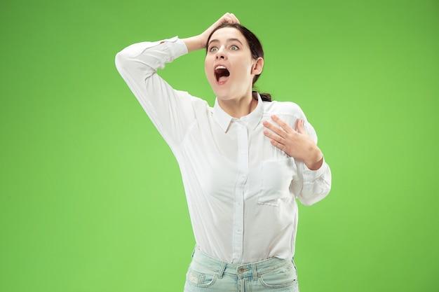 Schönes weibliches halbes längenfrontporträt lokalisiert auf grünem studiohintergrund. junge emotionale überraschte frau, die mit offenem mund steht.