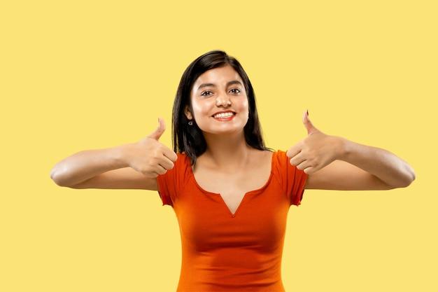 Schönes weibliches halbes längenporträt lokalisiert. junge emotionale indische frau im kleid, das das zeichen von ok zeigt. negativer raum. gesichtsausdruck, menschliches gefühlskonzept.