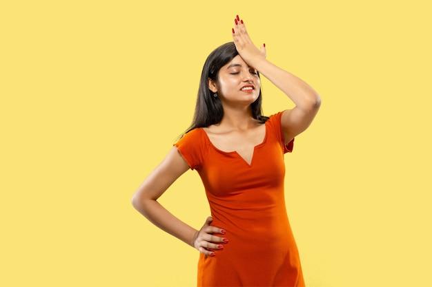 Schönes weibliches halbes längenporträt lokalisiert. junge emotionale indische frau im kleid, das sich an etwas erinnert. negativer raum. gesichtsausdruck, menschliches gefühlskonzept.