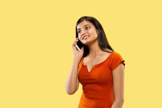 Schönes weibliches halblanges porträt auf gelbem studio