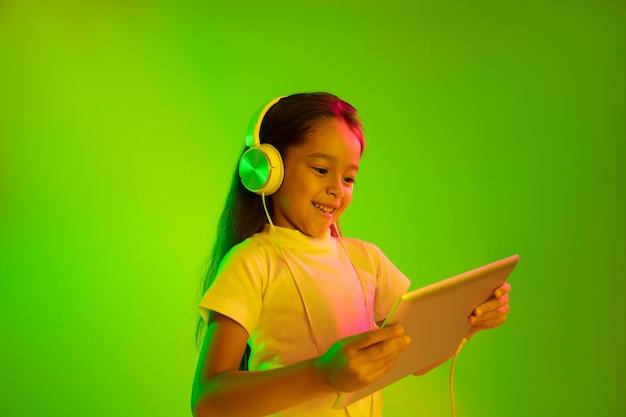 Schönes weibliches halblanges porträt lokalisiert auf grünem hintergrund im neonlicht. junges emotionales mädchen. menschliche emotionen, gesichtsausdruckkonzept. trendige farben. verwenden des tablets für spiele, vlog, selfie.