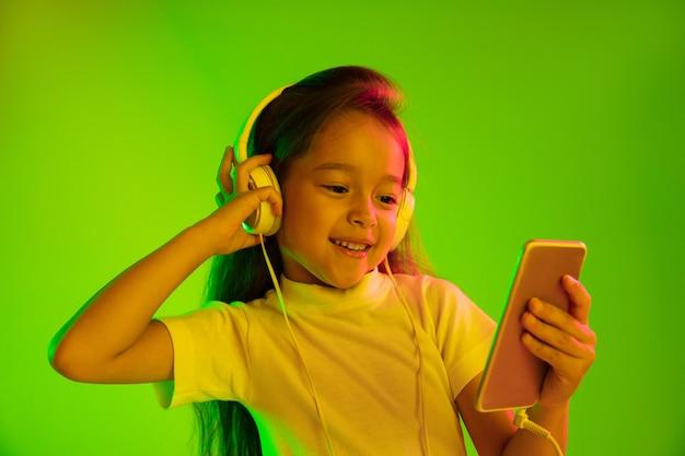Schönes weibliches halblanges porträt lokalisiert auf grünem hintergrund im neonlicht. junges emotionales mädchen. menschliche emotionen, gesichtsausdruckkonzept. verwenden des smartphones für vlog, selfie, chatten, spielen.