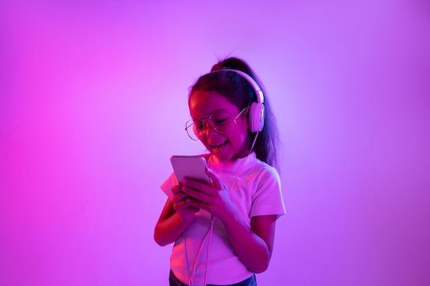 Schönes weibliches halblanges porträt lokalisiert auf lila hintergrund im neonlicht. emotionales mädchen in der brille. menschliche emotionen, gesichtsausdruckkonzept. musik hören, selfie machen, spielen.