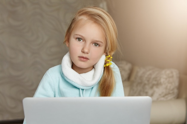 Schönes weibliches kind mit blondem haar, das internet auf ihrem laptop-computer surft