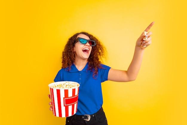 Schönes weibliches lockiges modell im hemd, das mit popcorn zeigt