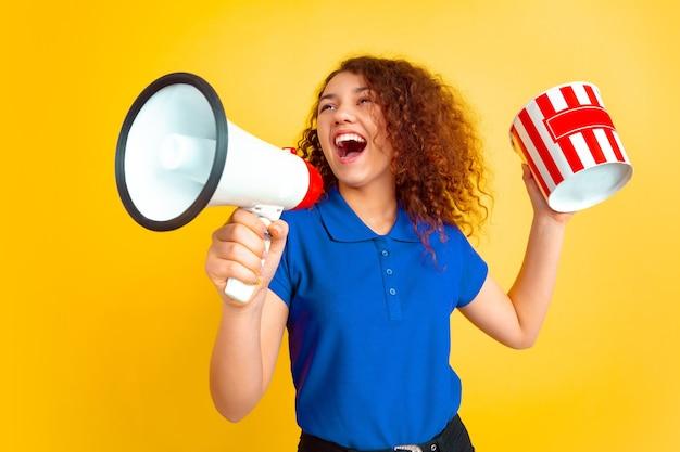 Schönes weibliches lockiges modell im hemd mit megaphon und popcorn-eimer