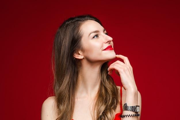 Schönes weibliches model im weißen kleid denkt über etwas interessantes nach und lächelt