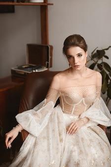 Schönes weibliches model trägt ein vintage-hochzeitskleid mit langen ärmeln drinnen stilvolle junge braut...