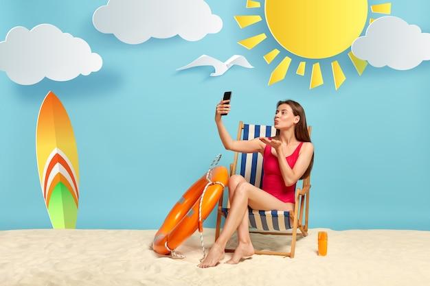 Schönes weibliches modell bläst luftkuss an der smartphone-kamera, macht selfie, posiert am strandkorb, trägt roten bikini