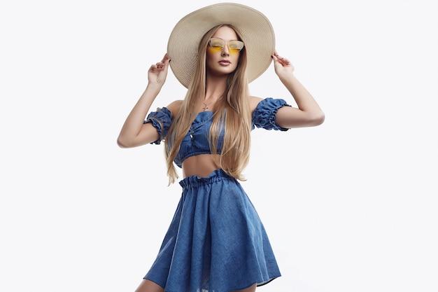 Schönes weibliches modell, das im blauen kleid und im breiten hut aufwirft