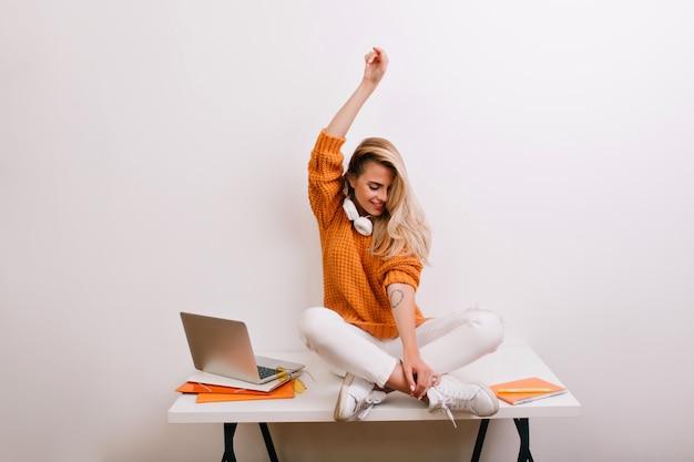 Schönes weibliches modell, das nahe weiße wand nach langer arbeit mit laptop aufwirft