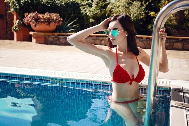 Schönes weibliches modell des langen haares, das durch den pool, außenporträt aufwirft. im sommer entspannen