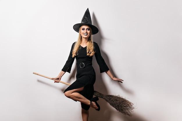 Schönes weibliches modell im karnevalskostüm, das auf weißer wand lacht. glückselige hexe, die mit besen auf halloween-party aufwirft.
