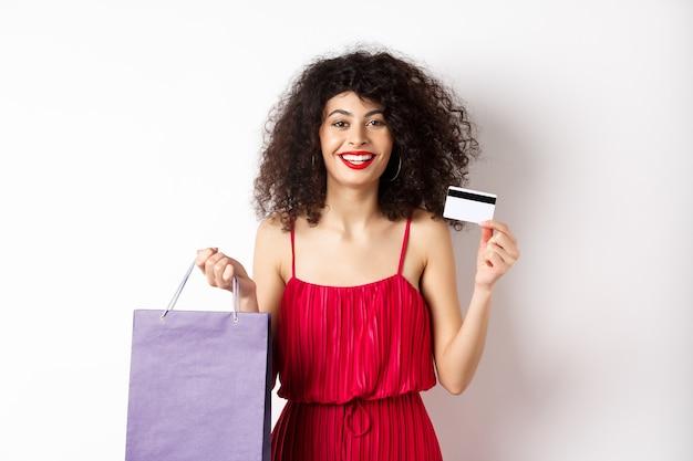 Schönes weibliches modell mit lockigem haar, rotem kleid, einkaufstasche und plastikkreditkarte, weißer hintergrund zeigend.