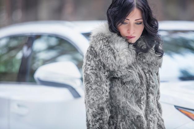 Schönes weibliches modell zart und traurig im fell auf der oberfläche des autos