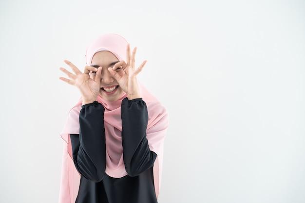 Schönes weibliches muslimisches modell in der modernen kurung und im hijab, eine moderne lebensstilkleidung für muslimische frauen, die auf weißer wand lokalisiert werden. beauty- und hijab-modekonzept. porträt in halber länge