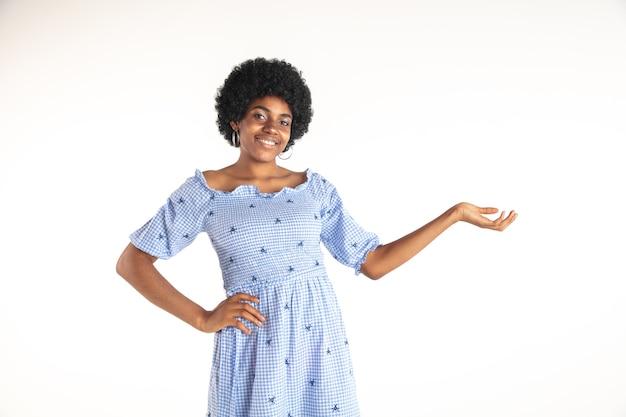 Schönes weibliches porträt der halben länge auf weißer wand. junge emotionale afroamerikanerfrau im blauen kleid. gesichtsausdruck, menschliches gefühlskonzept. gestikulieren, einladen, zeigen.