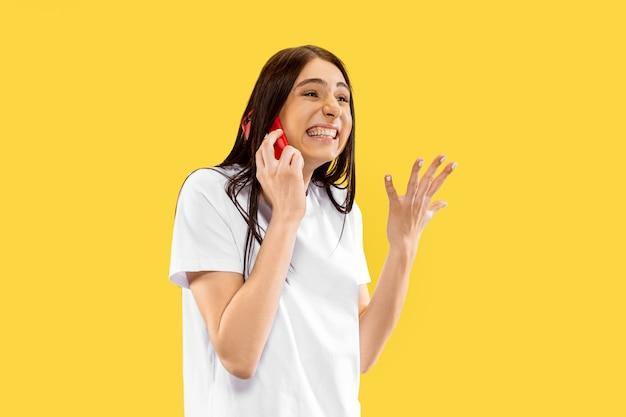 Schönes weibliches porträt der halben länge lokalisiert auf gelbem raum. junge lächelnde frau. gesichtsausdruck, sommer, wochenende, resort-konzept