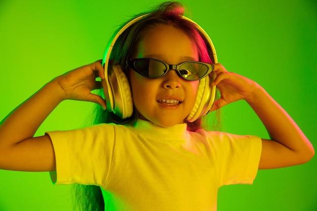 Schönes weibliches porträt der halben länge lokalisiert auf grünem hintergrund im neonlicht. junges emotionales jugendlich mädchen in der sonnenbrille. menschliche emotionen, gesichtsausdruckkonzept. trendige farben. tanzen, lächeln.