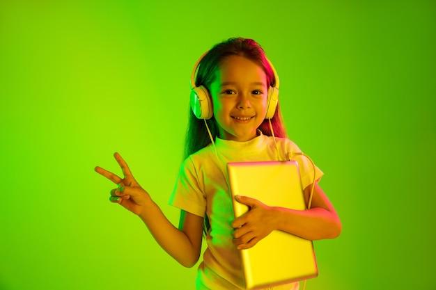 Schönes weibliches porträt der halben länge lokalisiert auf grünem hintergrund im neonlicht. junges emotionales jugendlich mädchen. menschliche emotionen, gesichtsausdruckkonzept. trendige farben. tablette halten und lächeln.
