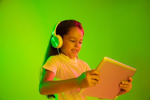 Schönes weibliches porträt der halben länge lokalisiert auf grünem hintergrund im neonlicht. junges emotionales mädchen. menschliche emotionen, gesichtsausdruckkonzept. trendige farben. verwenden des tablets für spiele, vlog, selfie.
