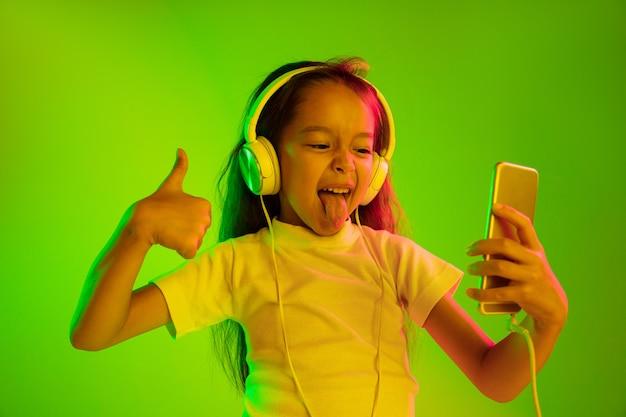 Schönes weibliches porträt der halben länge lokalisiert auf grünem hintergrund im neonlicht. junges emotionales mädchen. menschliche emotionen, gesichtsausdruckkonzept. verwenden des smartphones für vlog, selfie, chatten, spielen.
