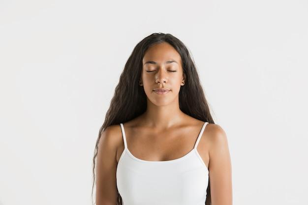 Schönes weibliches porträt der halben länge lokalisiert auf weißem studiohintergrund. junge emotionale afroamerikanerfrau mit langen haaren. gesichtsausdruck, menschliches gefühlskonzept. beruhige dich mit geschlossenen augen.