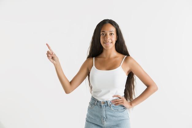 Schönes weibliches porträt der halben länge lokalisiert auf weißem studiohintergrund. junge emotionale afroamerikanerfrau mit langen haaren. gesichtsausdruck, menschliches gefühlskonzept. leere leertaste anzeigen.