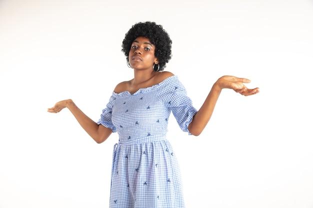 Schönes weibliches porträt der halben länge lokalisiert auf weißer wand. junge emotionale afroamerikanerfrau im blauen kleid. gesichtsausdruck, menschliches gefühlskonzept. unwissenheit, unsicherheit.