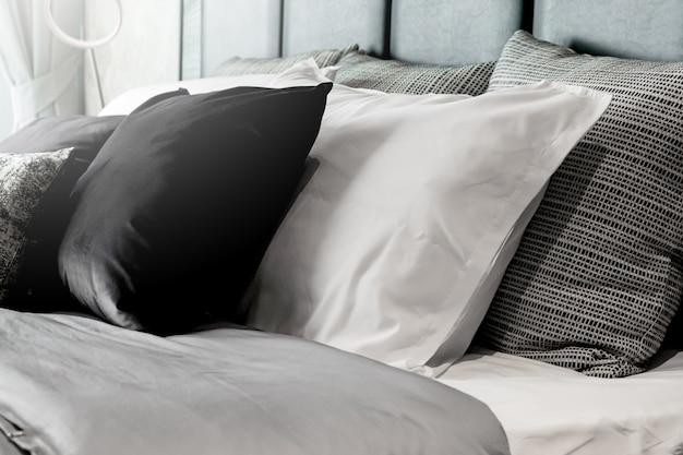 Schönes weiches kissen und decke mit weißem gemütlichem bett im modernen schlafzimmer
